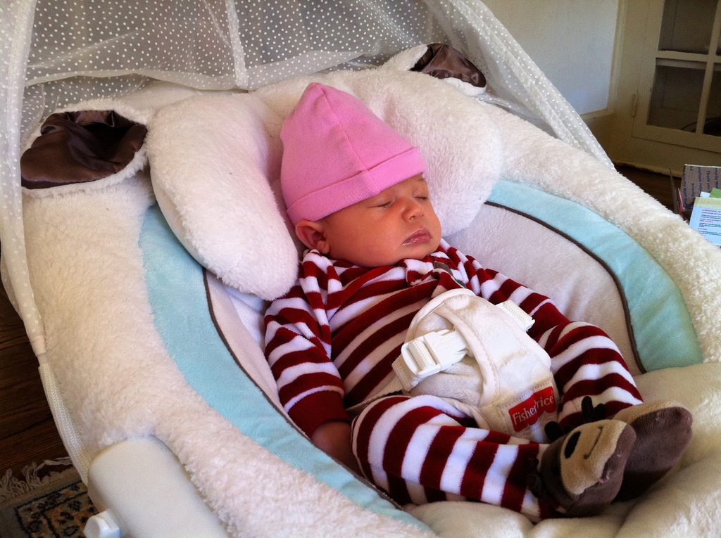Newborn baby in jammies sleeping in swing